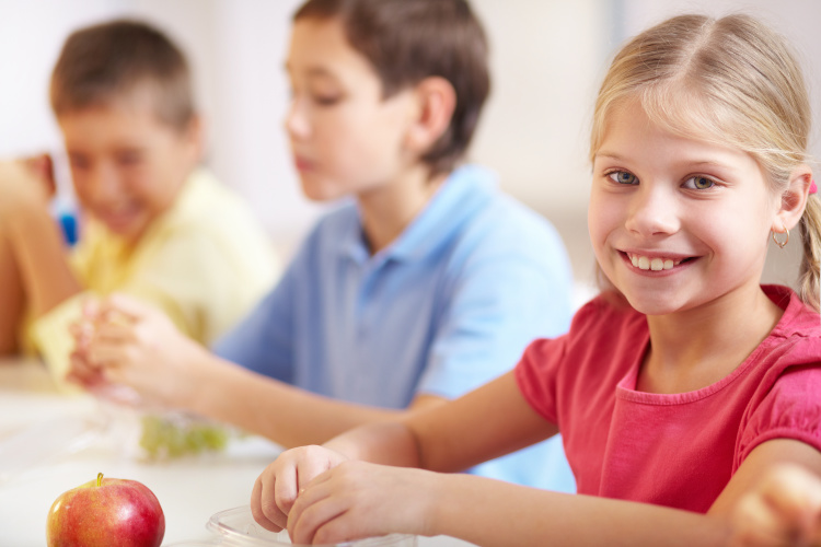 Group of kids having lunch during break with focus on smiling girl looking at camera