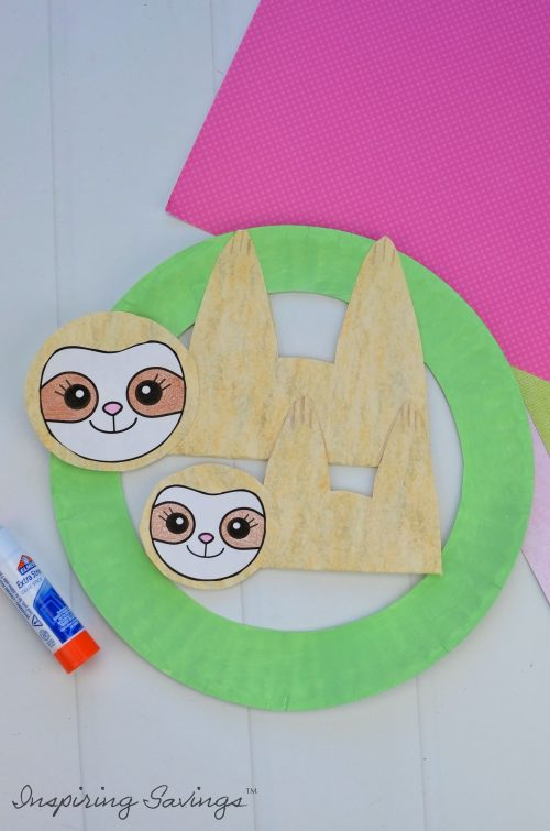 Adding baby sloth to mommy sloth on green paper plate wreath for Mother's Day Card