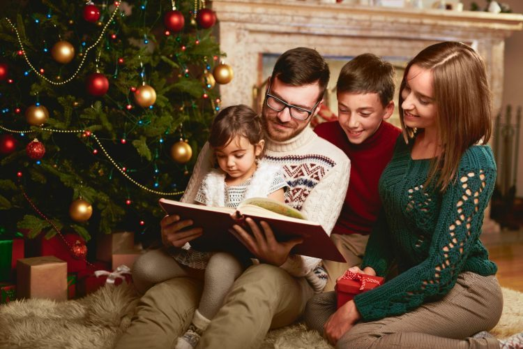 Happy Family reading by christmas tree