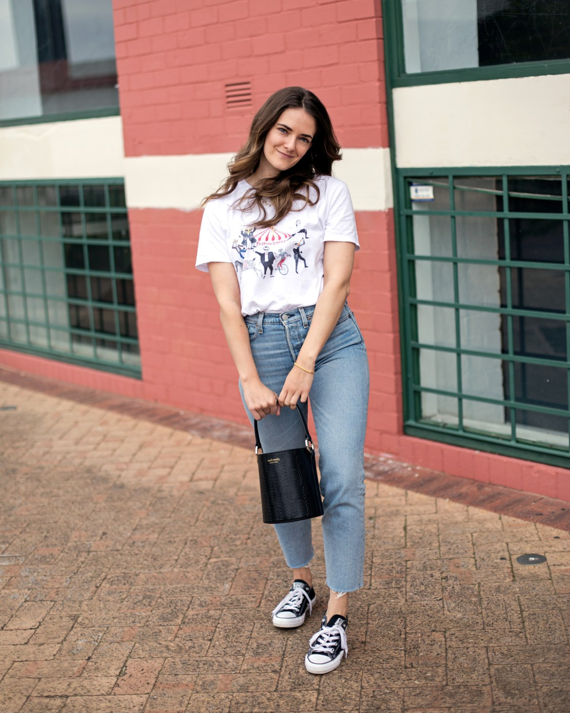 Meli Melo Santina bucket bag in black worn by fashion blogger Jenelle Witty from Inspiring Wit. With Unfortunate Portrait graphic tee, Levi's Wedgie jeans and Converse sneakers from Shopbop