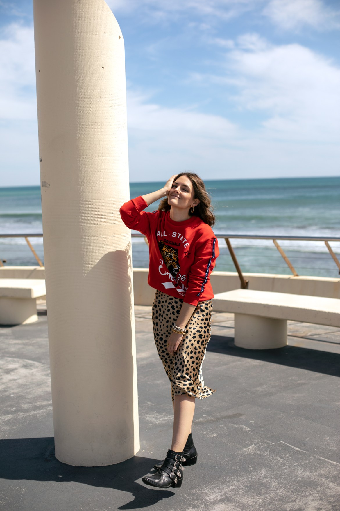 Jenelle Witty from Inspiring Wit in Realisation Par the Namoi Wild Things leopard print skirt with red leopard sweater from Superdry and Toga Pulla buckle boots