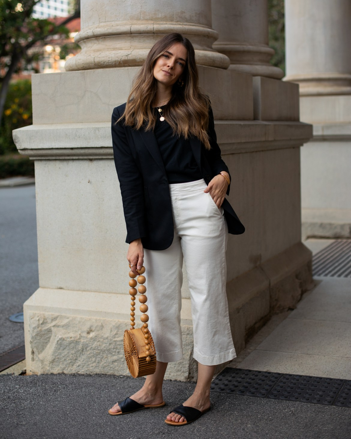 Black blazer, cream pants outfit with black slides and bamboo bag idea for everyday