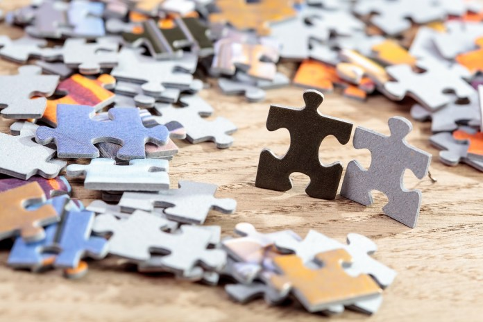 Concept of friendship: closeup of black and grey  jigsaw puzzle pieces on table. Shallow depth of field