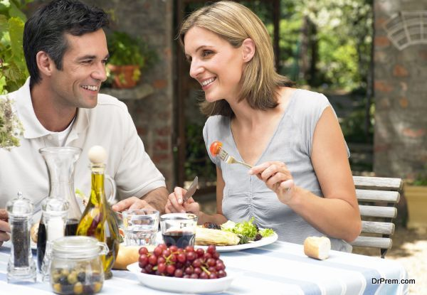 Couple eating lunch in garden, smiling