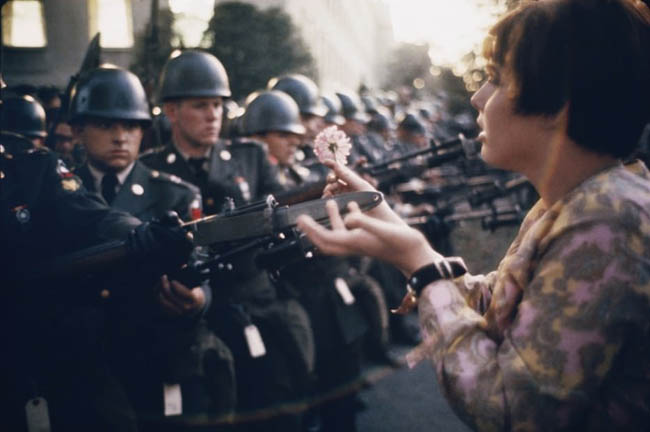 17 year old Jan Rose Kasmir offers a flower to soldiers during the Pentagon anti-war protest in 1967.