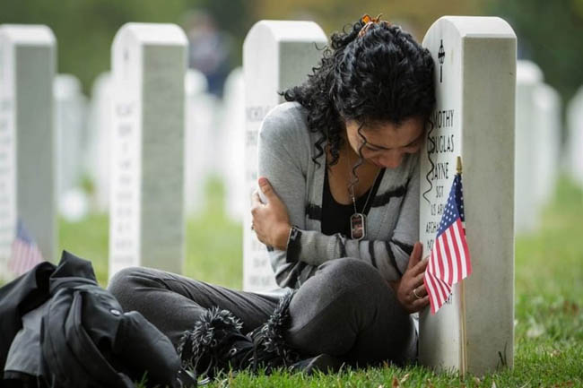Thania Sayne leans on the headstone of her husband the day before their wedding anniversary on 16 October 2013.