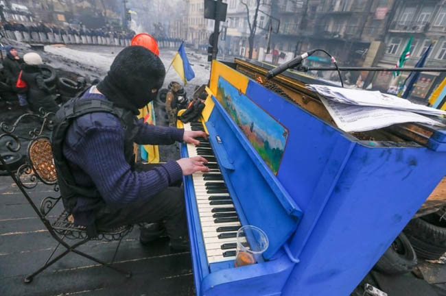 Protester plays piano over the sounds of chaos, with riot police in the backdrop.