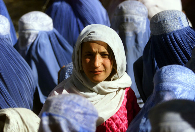 A young Afghan woman shows her face in public for the first time after 5 years of Taliban Sharia law. [2001]