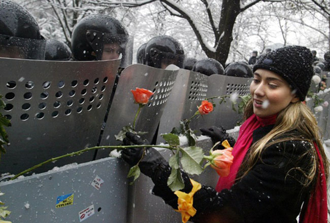 A Ukrainian woman places carnations into shields of anti-riot policemen