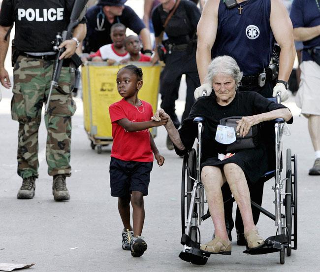 Tanisha Blevin, 5, holds the hand of fellow Hurricane Katrina victim Nita LaGarde, 105