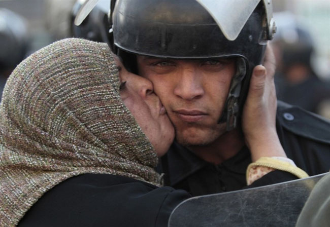 An Egyptian woman kisses a policeman, who had refused to fire on protestors