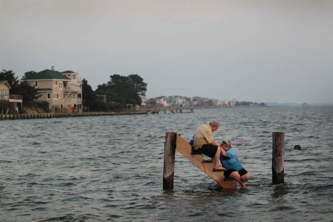 Billy Stinson comforts his daughter on the steps where their cottage once stood before it was destroyed by Hurricane Irene