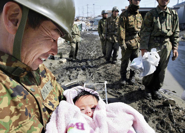 A 4-month-old baby girl is rescued from the rubble four days after the Japanese tsunami. [2011]
