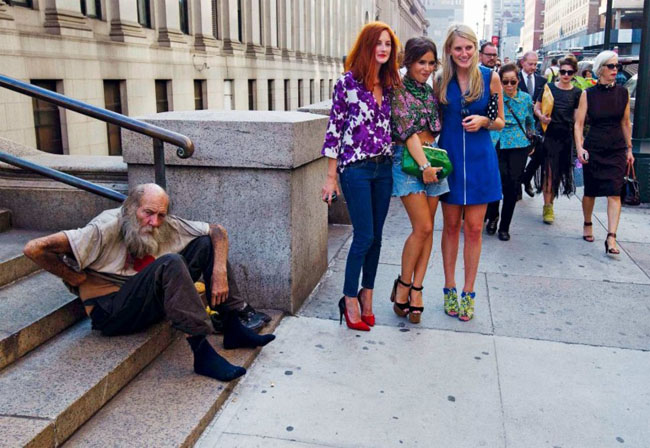 21st century photos - Three young women from the New York Fashion Week pose next to a homeless man. [2012]