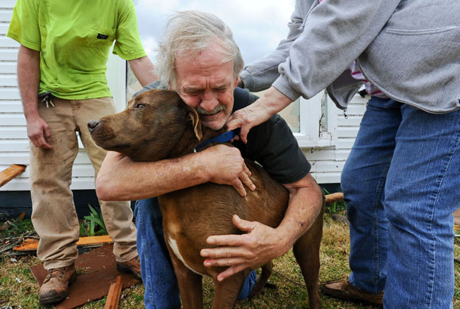 Greg Cook hugs his dog Coco after finding her inside his destroyed home in Alabama following the Tornado. [2012]