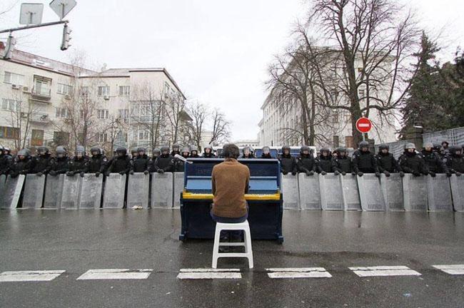 21st century photos - Markiyan Matsekh plays piano for police during the Ukranian revoloution. [2014]