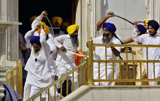 Sikhs wield swords during their clash inside the complex of the holy Sikh shrine, the Golden Temple, in the northern Indian city of Amritsar.