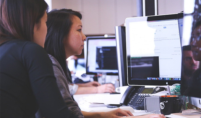 A person creating a quality landing page on a computer with a professional designer helping them out.