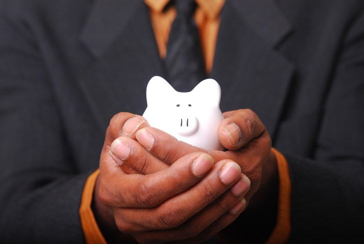 man in a suit with piggy bank on hands
