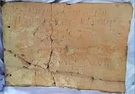 """Tegolone in terracotta (100- 90 a.C) Alt. 66: largh. 94. Sui due lati lunghi si contrappongono due iscrizioni, l'una in latino, l'altra in osco. Nella fascia centrale ci sono due orme di calzari, incrociate tra loro. Il testo: """"hn. sattieiies deftri / seganatted. plavted Herenneis. Amica / signavit. qando ponebamus. tegila"""" (trad.: Deftri schiava di Herennio Sattio ha firmato con il piede Amica, schiava di Herennio, ha firmato quando ponevamo le tegole"""")"""