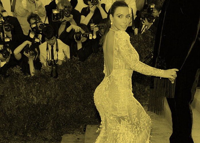 Reality TV star Kim Kardashian turns to look over her shoulder on the red carpet, surrounded by paparazzi