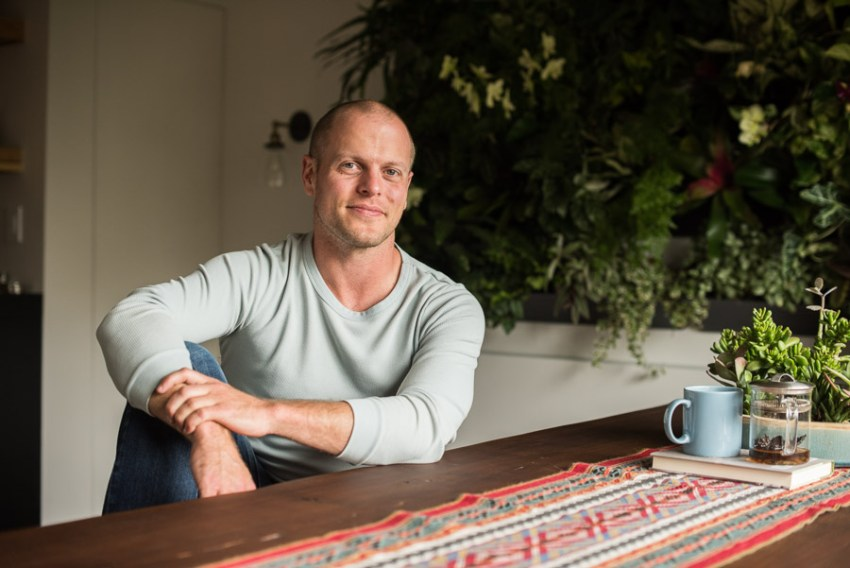 Tim Ferriss indoors. Close to his tea and books, smiling.