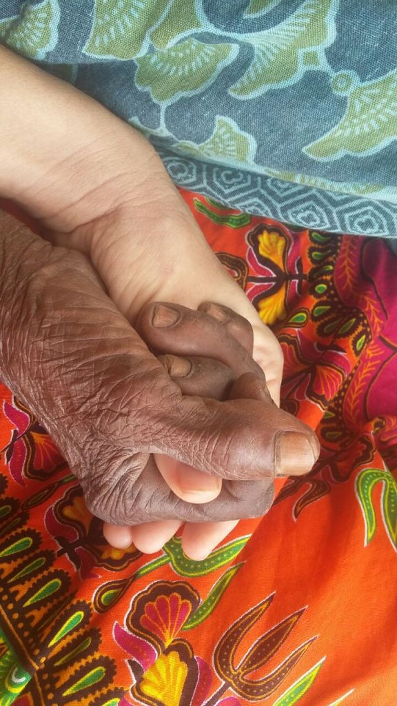 Older person's hand holding younger person's hand