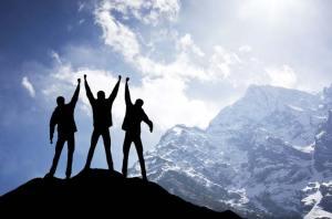 3 hombres alzando sus manos sobre una cumbre