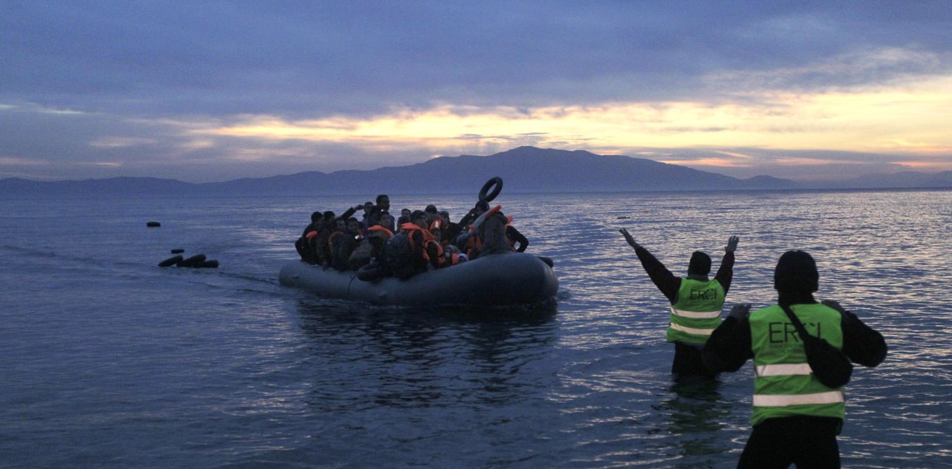 Volunteers of an NGO direct refugees and migrants arriving in a dinghy from Turkey to the coast of Mytilini, on the island of Lesvos, Greece, 17 February 2016.