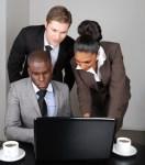 Multi-ethnic business team working on laptop