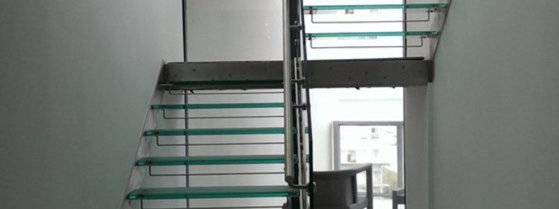 Acciaio inox per struttura e corrimano, vetro extra chiaro per il parapetto, vetro satinato antiscivolo per i gradini
