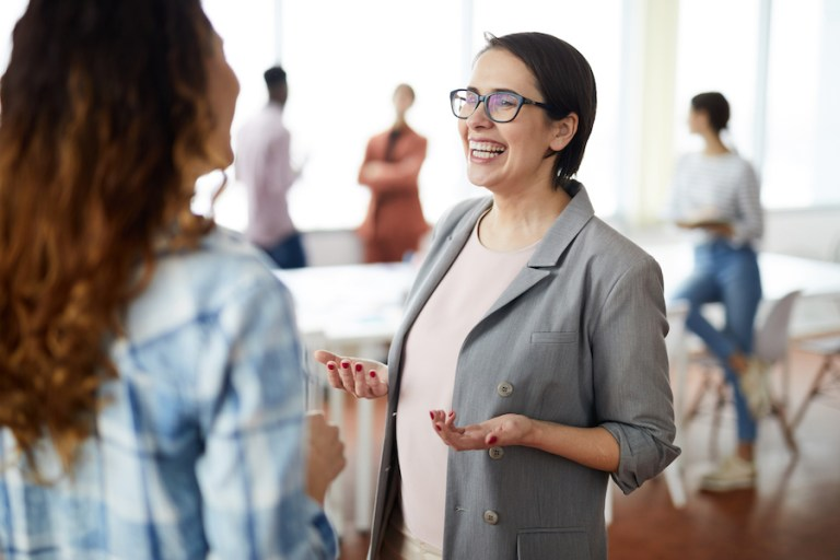 Waist up portrait of successful businesswoman smiling happily while talking to colleague in modern office