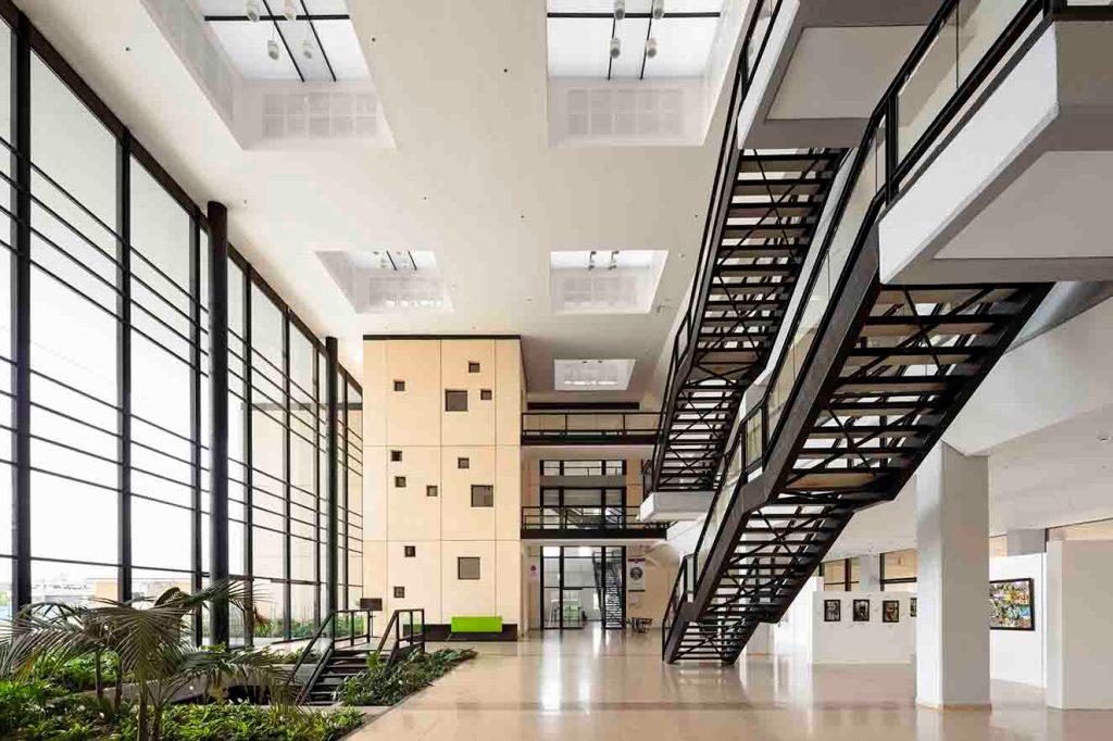 Caudales de luz natural iluminan el foyer gracias al ventanal en la fachada principal que abarca tres niveles. El jardín interior otorga calidez al espacio. El piso es de baldosa de granito. Fotografía: Enrique Guzmán G.