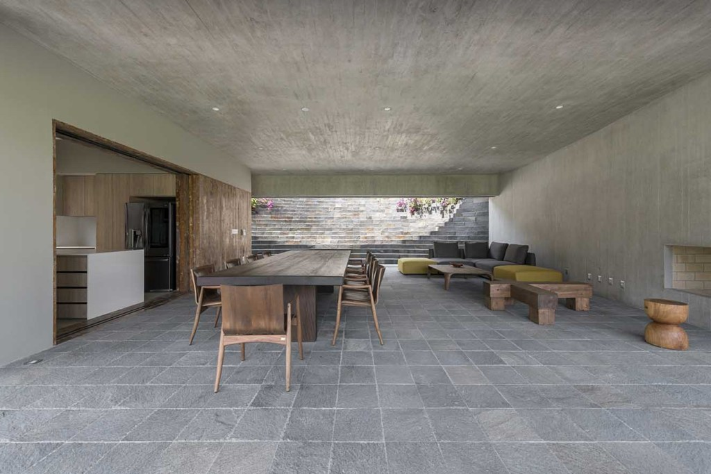 Para el piso del área social se escogió piedra gris en formato cuadrado que juega con el techo y paredes de concreto a la vista. Muebles de madera maciza tanto para el comedor como en la sala  visten el espacio que sorprende por su austeridad. La arquitectura habla por sí sola. Fotografía: Renzo Rebagliati.