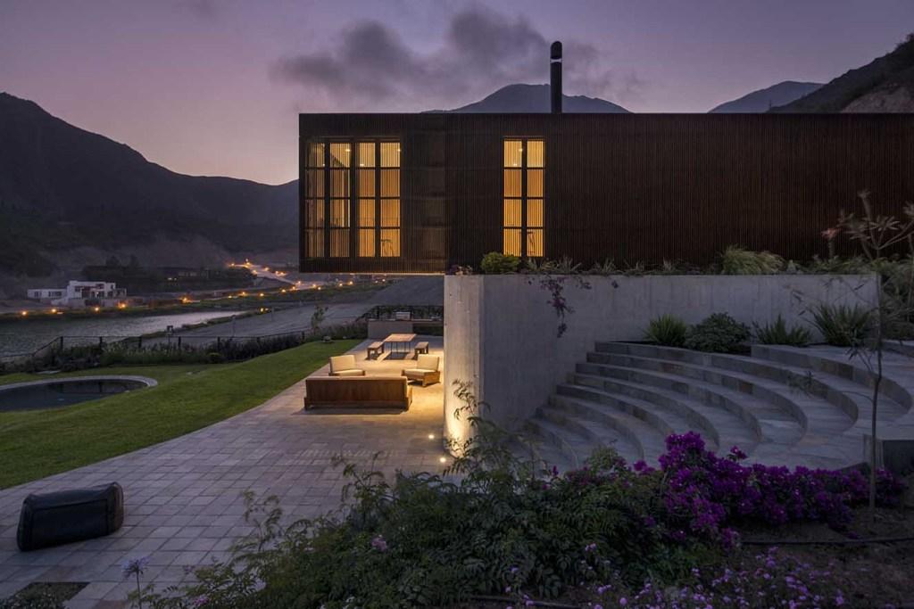 En la noche, el volumen superior acabado en madera se convierte en una caja de luz. Fotografía: Al atardecer el diseño de la iluminación transforma el aspecto de la casa  y le da  un carácter mágico. Fotografía: Renzo Rebagliati.