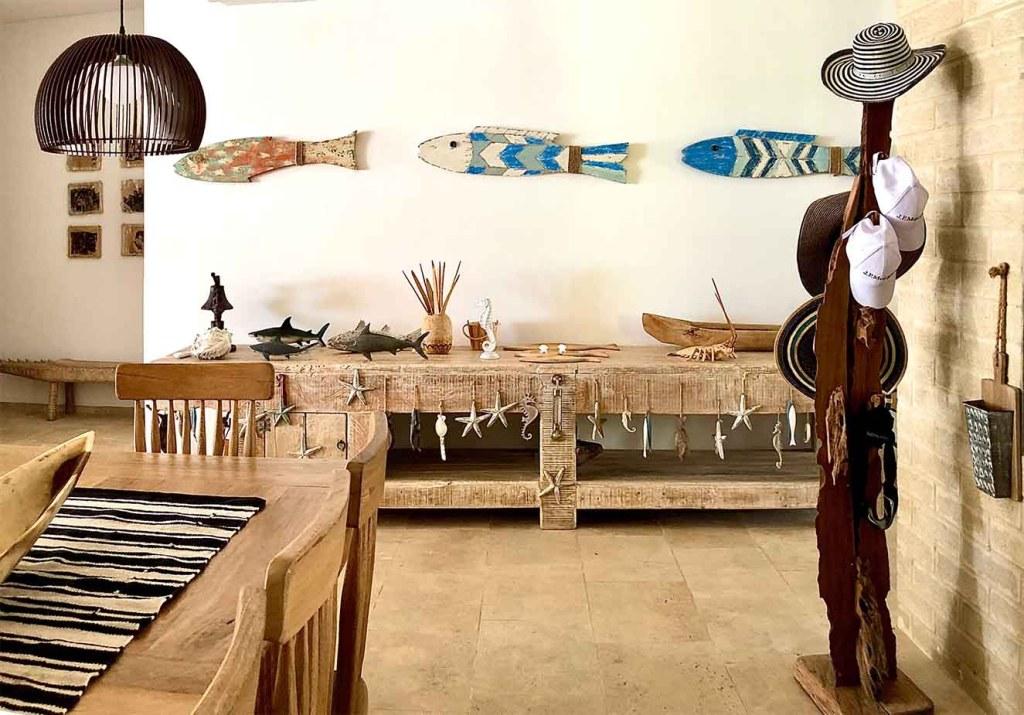 Una consola de madera como mueble recibidor con objetos inspirados en el tema marino refuerza el ambiente de casa de playa. Fotografía: Yvonne Meyer.