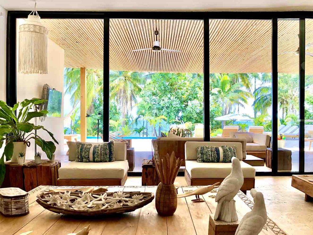 Ventanales de piso a techo y de lado a lado conectan la sala al interior de la casa con todo el paisaje y la vista al mar. Fotografía: Yvonne Meyer.
