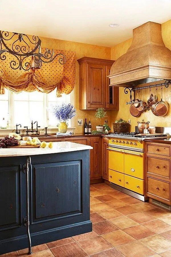 Charming Complexion A deep yellow tint with terra-cotta overtones bathes the plastered kitchen walls in a glow reminiscent of a Provencal sunset, and a prized French Lacanche range matches the color's intensity