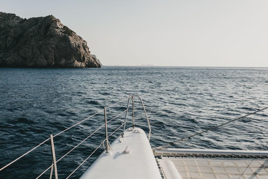 imagen profesional publicitaria del exterior de un catamaran para pasajeros navegando en las aguas de ibiza al atardecer