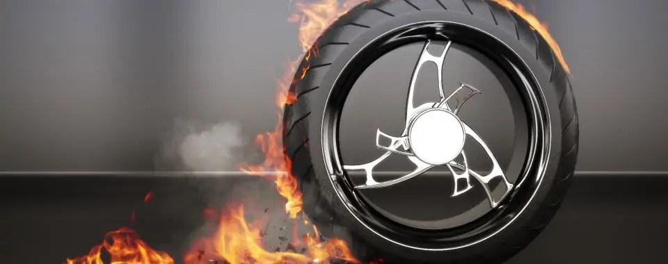 Desgaste de una llanta con llamas, humo y escombros para simbolizar la tracción o distracción