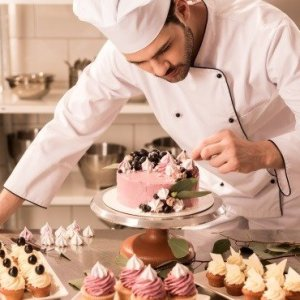 confectioner decorating cake in restaurant kitchen