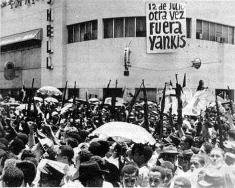 Armed populace in the street during revolution. Sign in background reads Yankees get out.