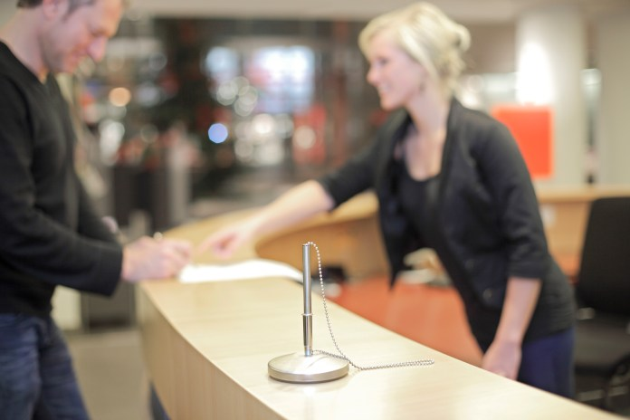Blond woman working at help desk speaking with a customer Freiburg Germany