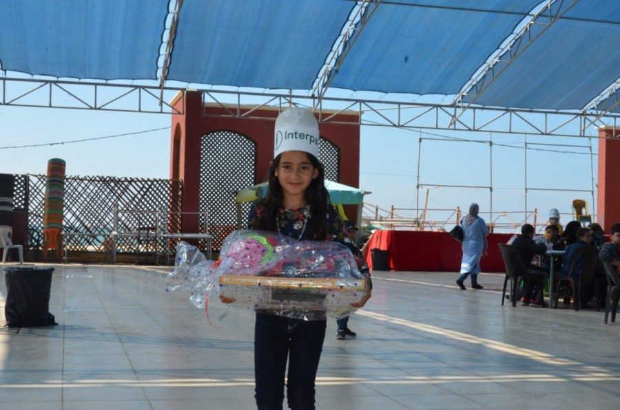 Hala receiving toys at Interpal's recreational event in Gaza