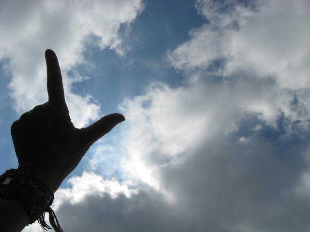 Fingers in front of clouds