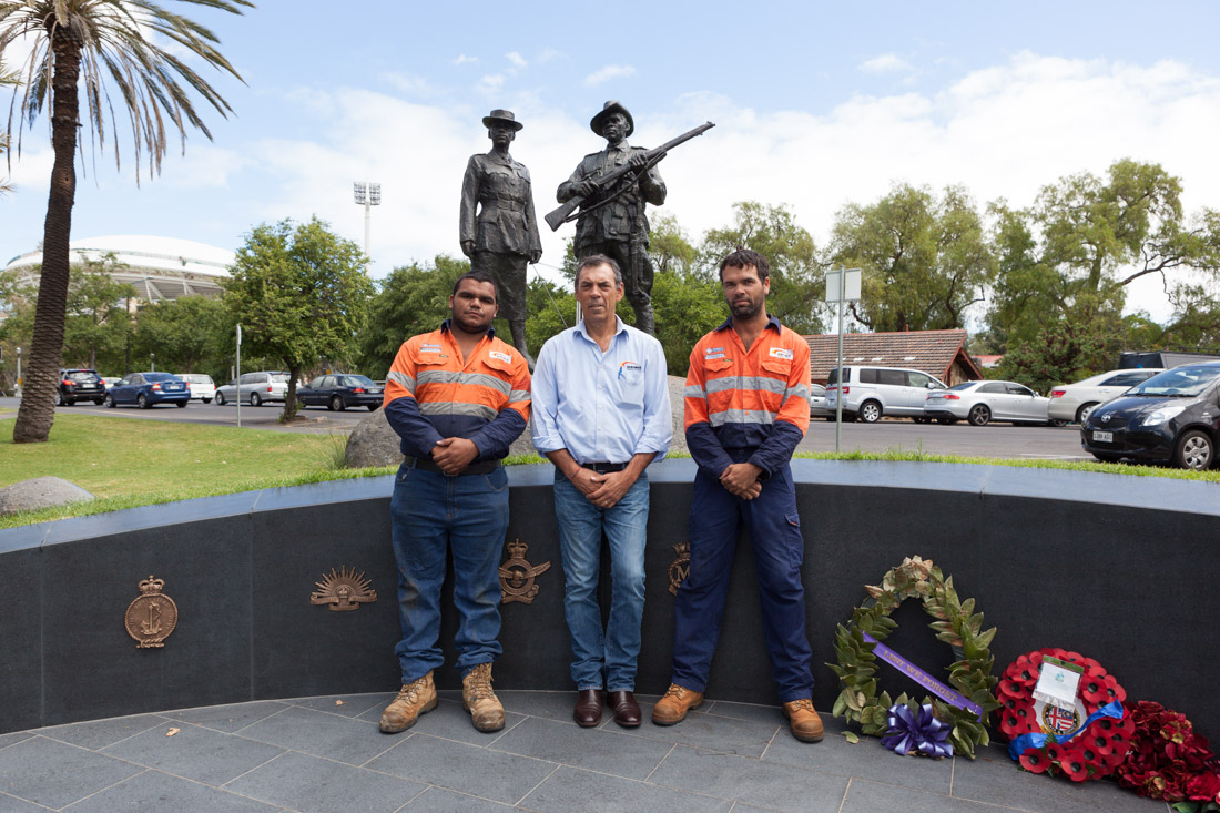 Intract employees standing proudly representing their Aboriginal heritage in front of ANZAC memorial