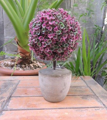 Arbol artificial con base de cemento, color verde con violeta. Foto completa.