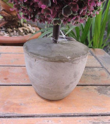 Arbol artificial con base de cemento, color verde con violeta. Foto de base.