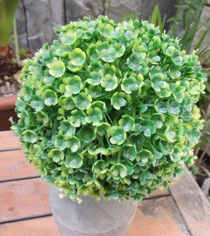 Arbol artificial con base de cemento, color verde. Foto de las hojas.