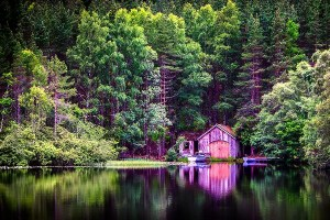 A boathouse is reflected in Loch Farr